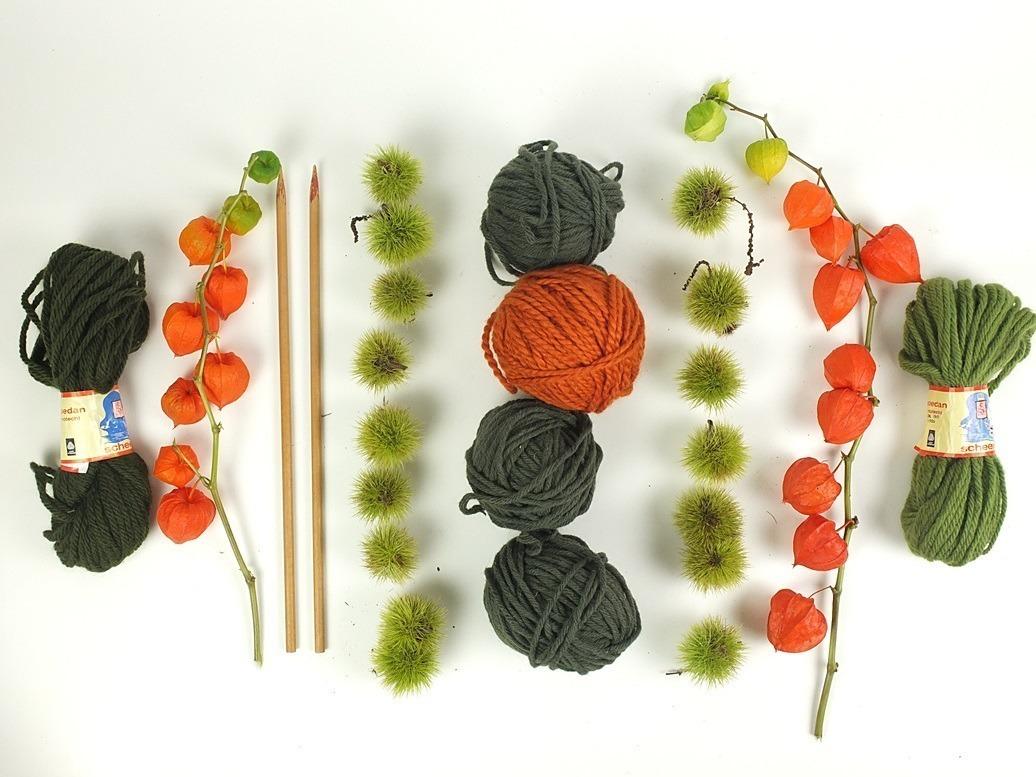 dikke wol en houten breipennen en oranje physalis
