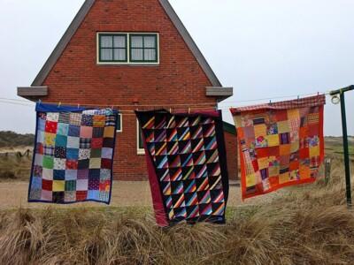 Drie quilts aan waslijn voor duinhuisje