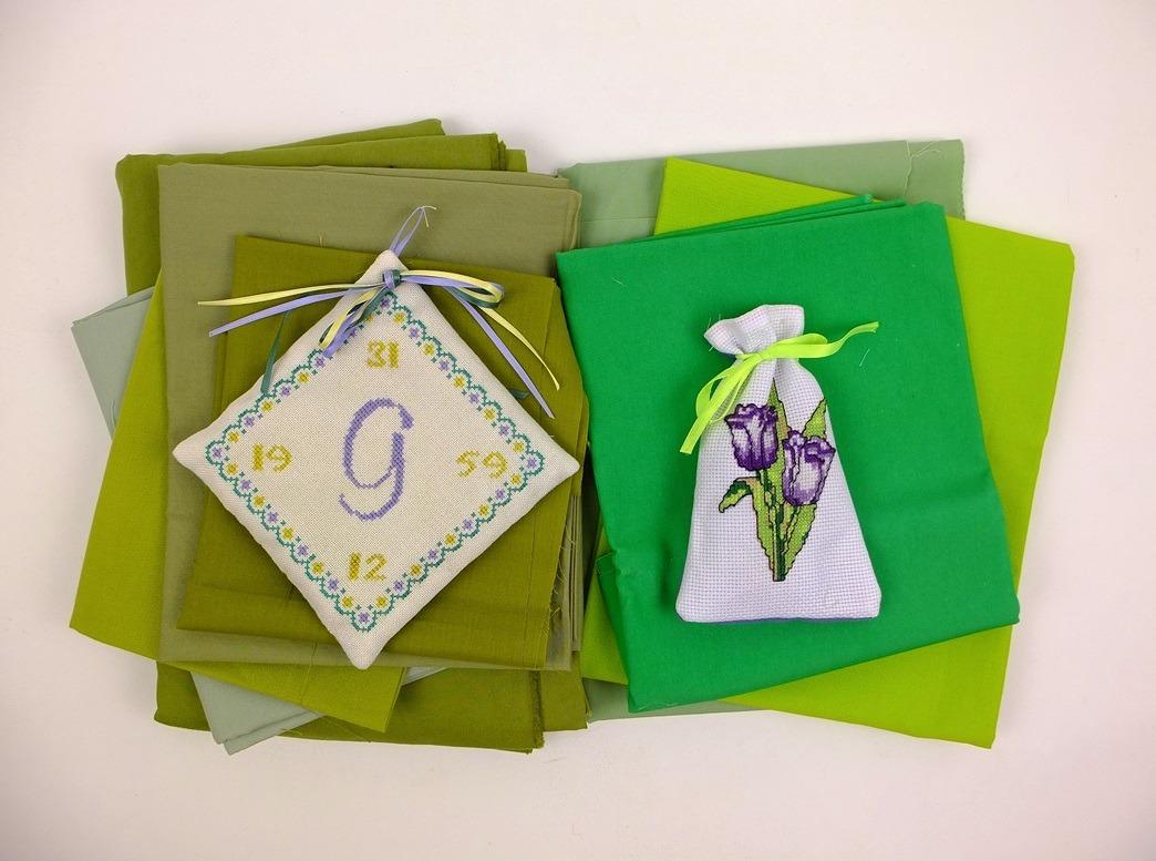 twee geborduurde lavendelzakjes op groene stof