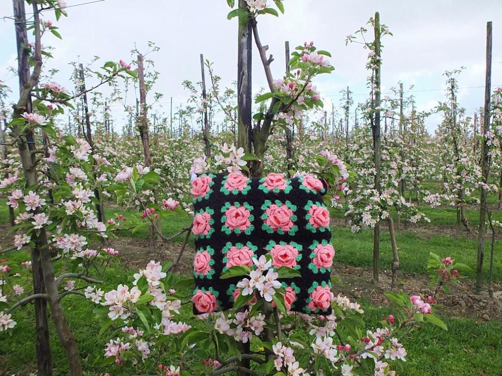 Kussen roze gehaakte bloemen in bloeiende boomgaard