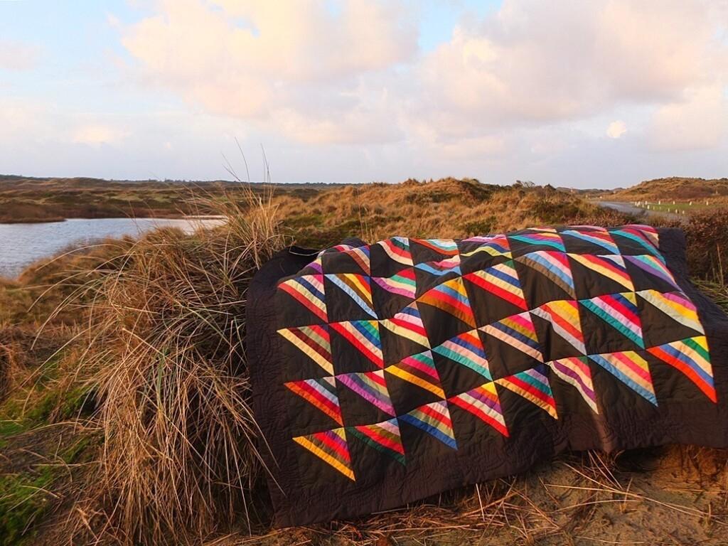 klelurige quilt in roman-stripes motief in de duinen met ochtendlicht