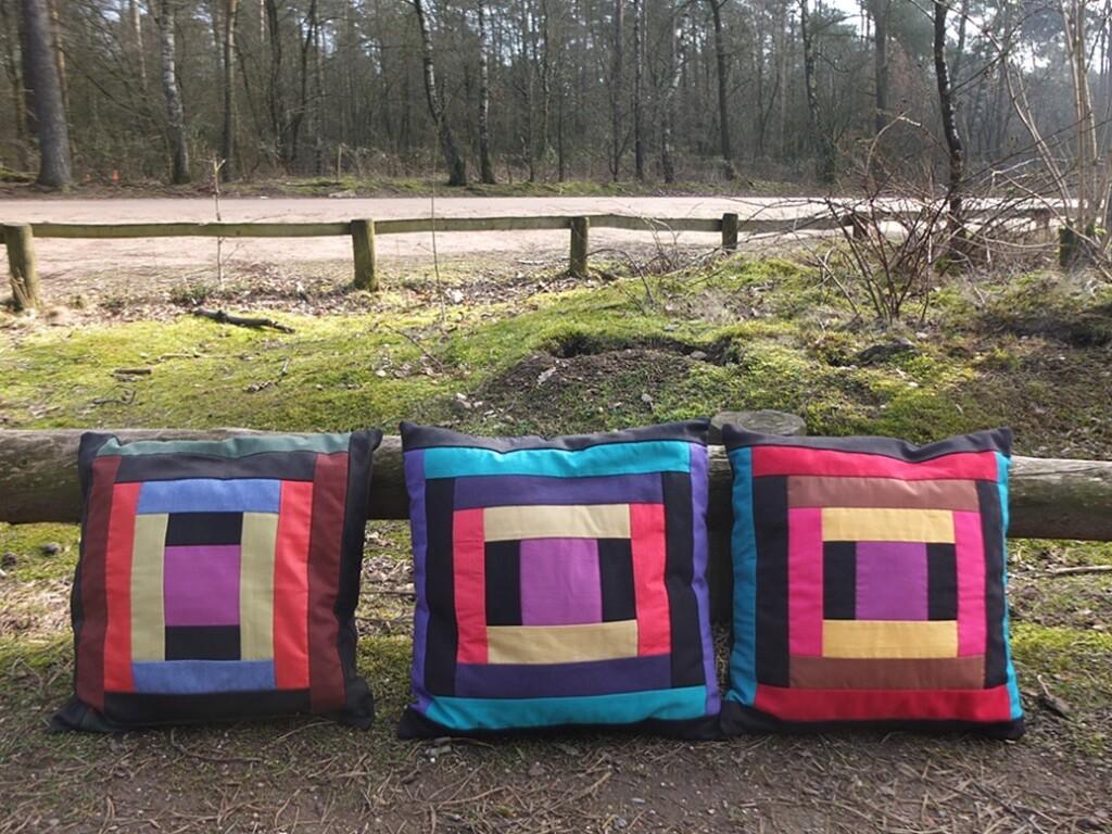 Drie log cabin kussentjes tegen hek