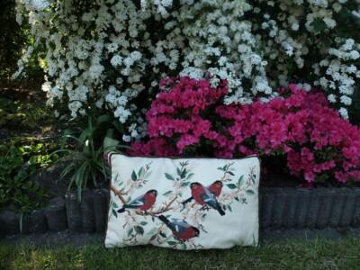 Geboruurde vogeltjes op kussen in tuin