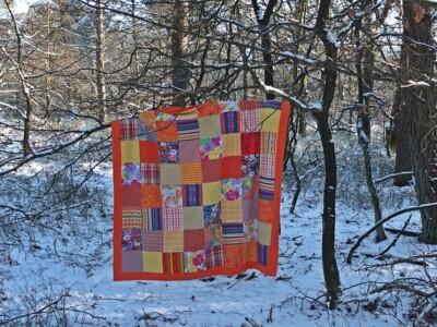 Oranje quilt in besneeuwd bos