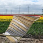 Beige gehaakte omslagdoek over hek bij bollenveld