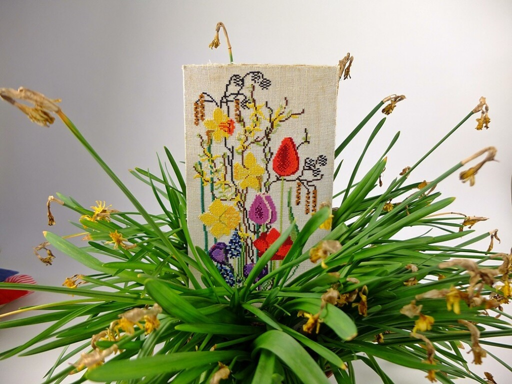Borduurwerk voorjaarsbloemen tussen uitgebloeide narcissen