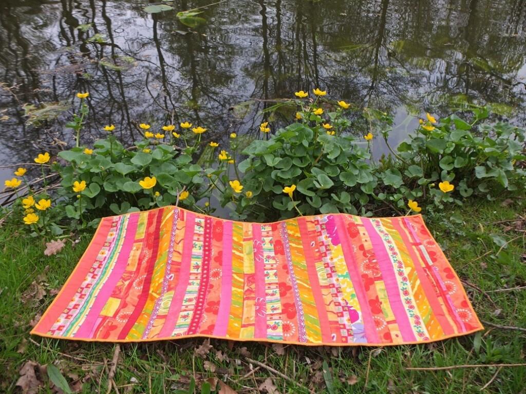 Oranje patchwork kleedje langs water met dotterbloemen