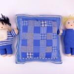 Twee gebreide poppetjes met blauw kussentje