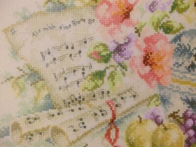 Detail geborduurd schilderij bladmuziek en bloemen