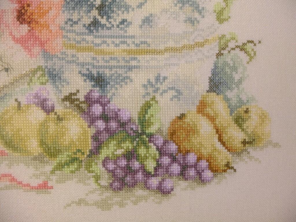 Detail geborduurd schilderij fruit bij vaas