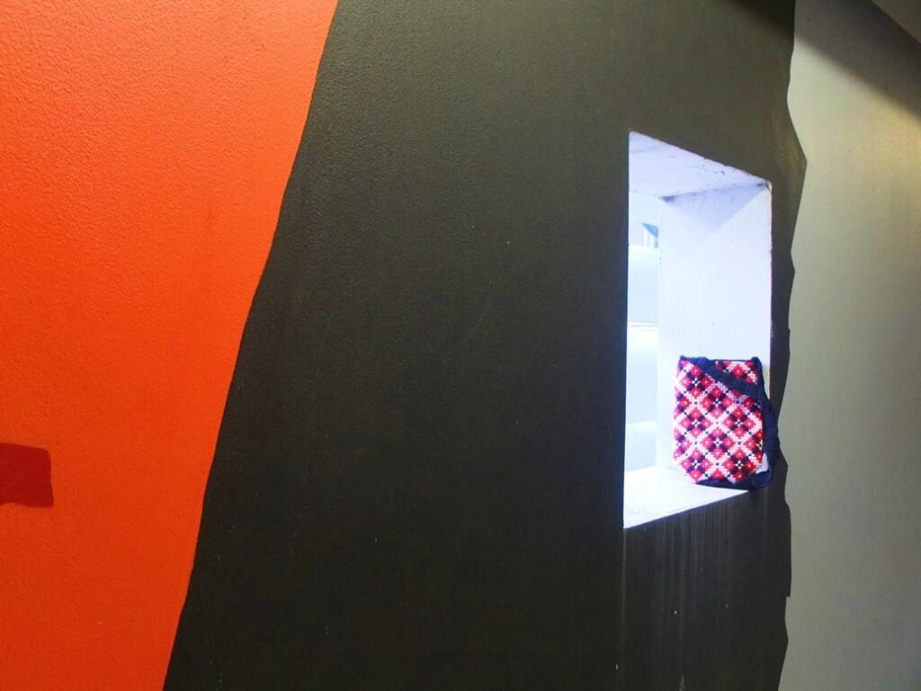 Tasje in rood en zwart in nis van parkeergarage