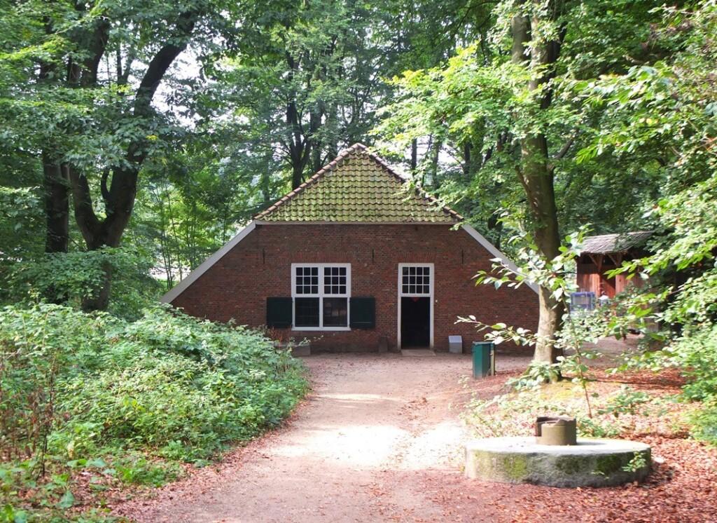 Klein boerderijtje tussen hoge bomen in Openluchtmuseum