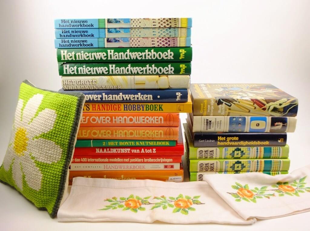Stapel dikke handwerkboeken met geborduurde bloemen