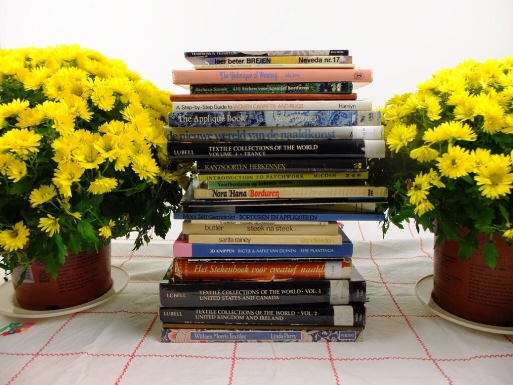 Stapel handwerkboeken tussen gele bolchrysanten