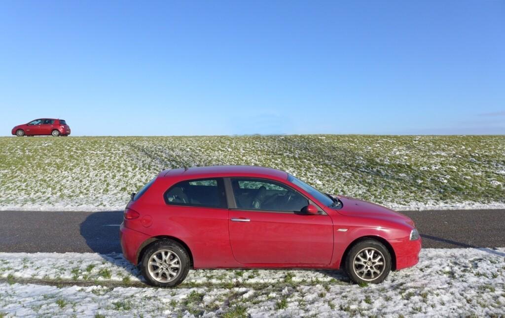 Rode auto's in de sneeuw op dijk