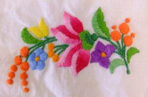 Geborduurd bloemetje in platsteek