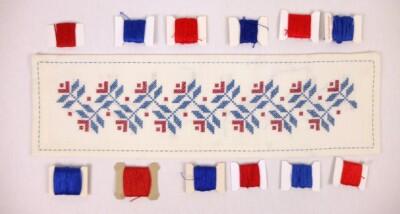 Geborduurd kleedje met klosjes rood en blauw garen