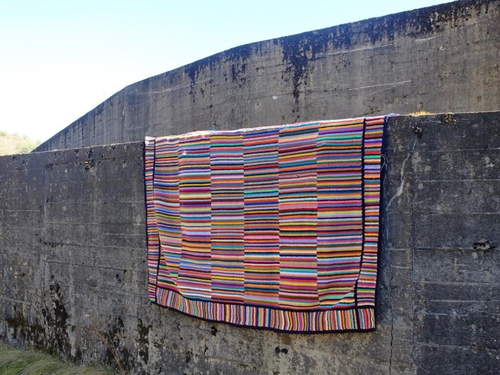 Gehaakte deken over grijze muur