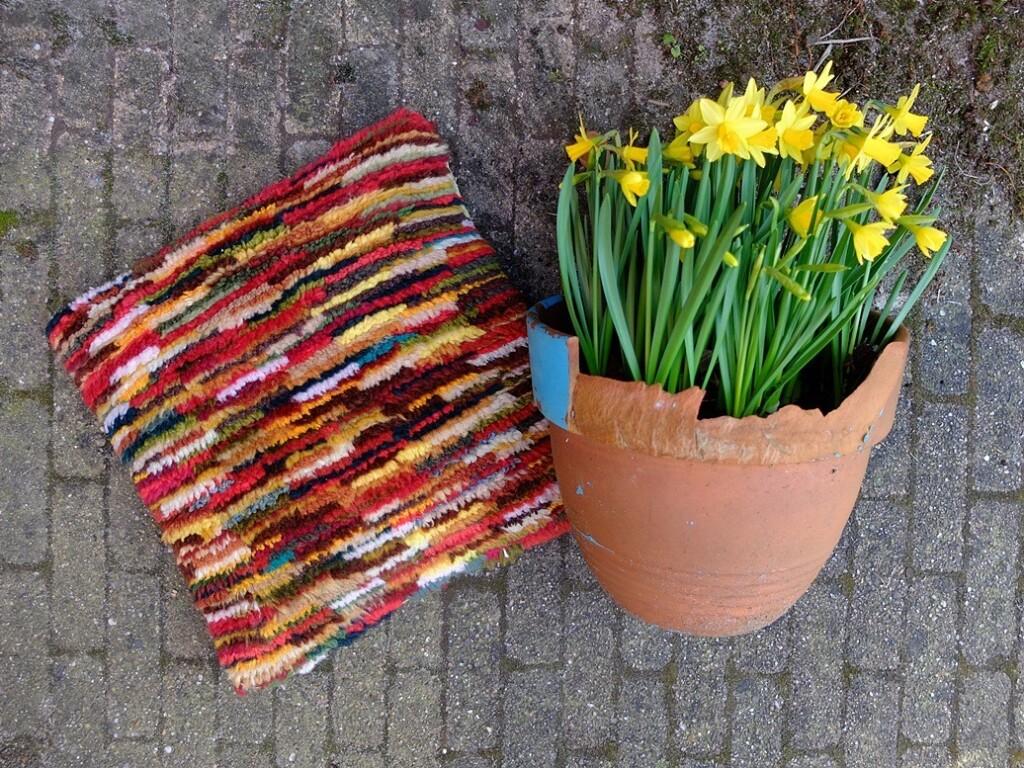 Kussen van geknoopte restjes met narcissen
