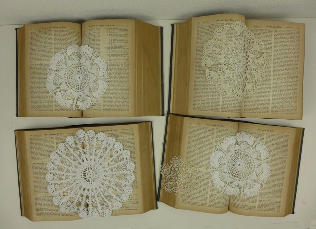 Vier oude boeken en kanten kleedjes