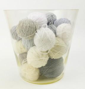 Bolletjes grijze en witte wol in glas