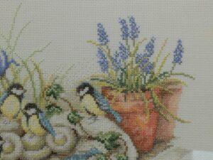 Detail borduurwerk koolmeesjes en blauwe druifjes