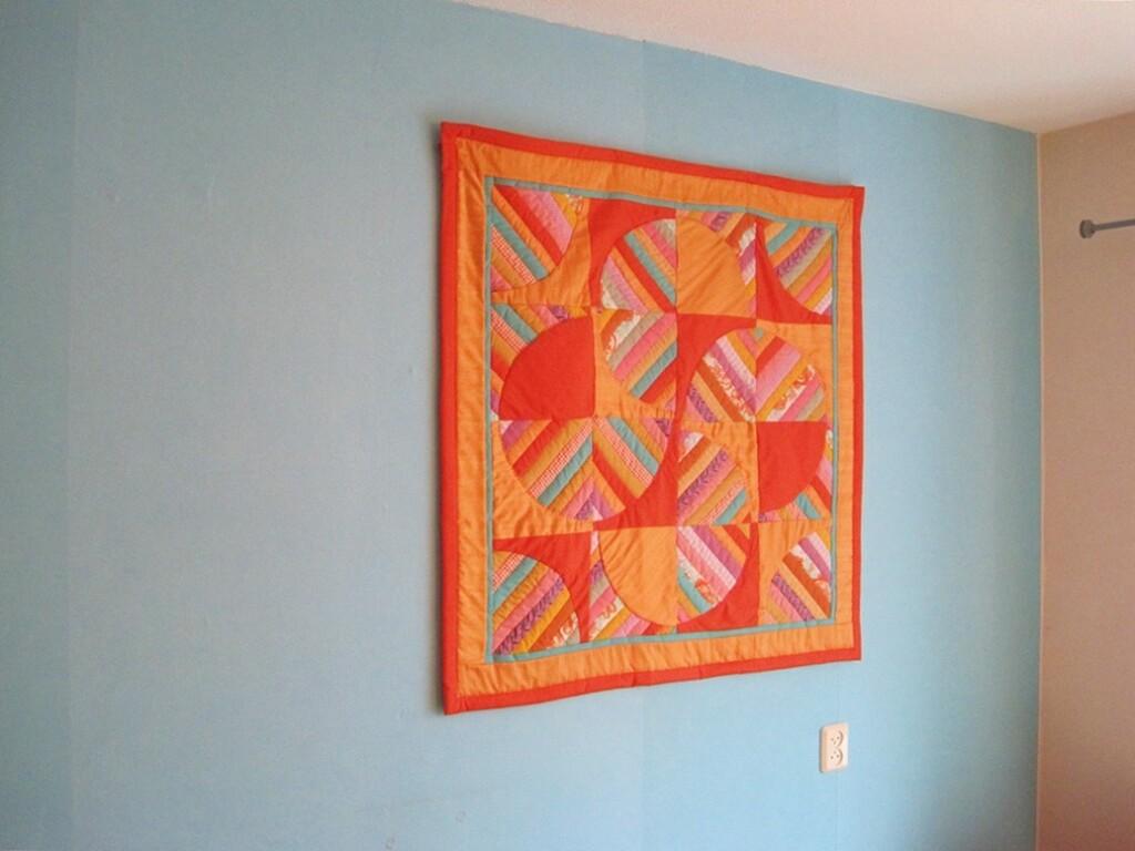 Oranje quilt op blauwe muur