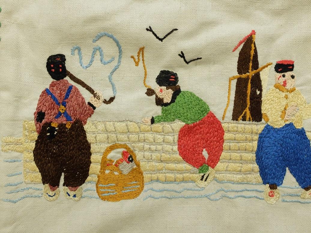 Borduurwerk in platsteek vissers bij muurtje