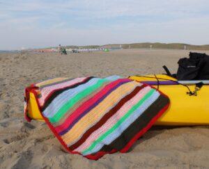 Gehaakte deken op gele kano