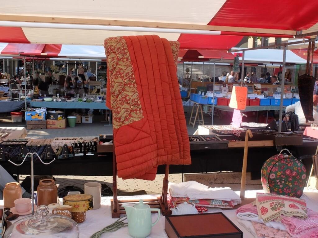 Oude doorgestikte deken op antiekmarkt