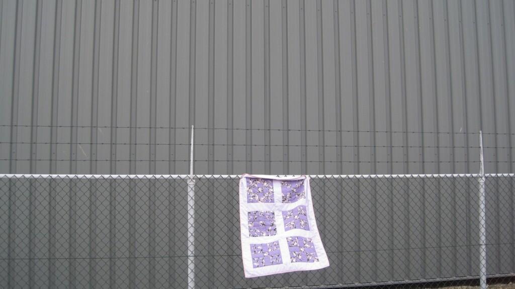 Sampler quilt aan hek