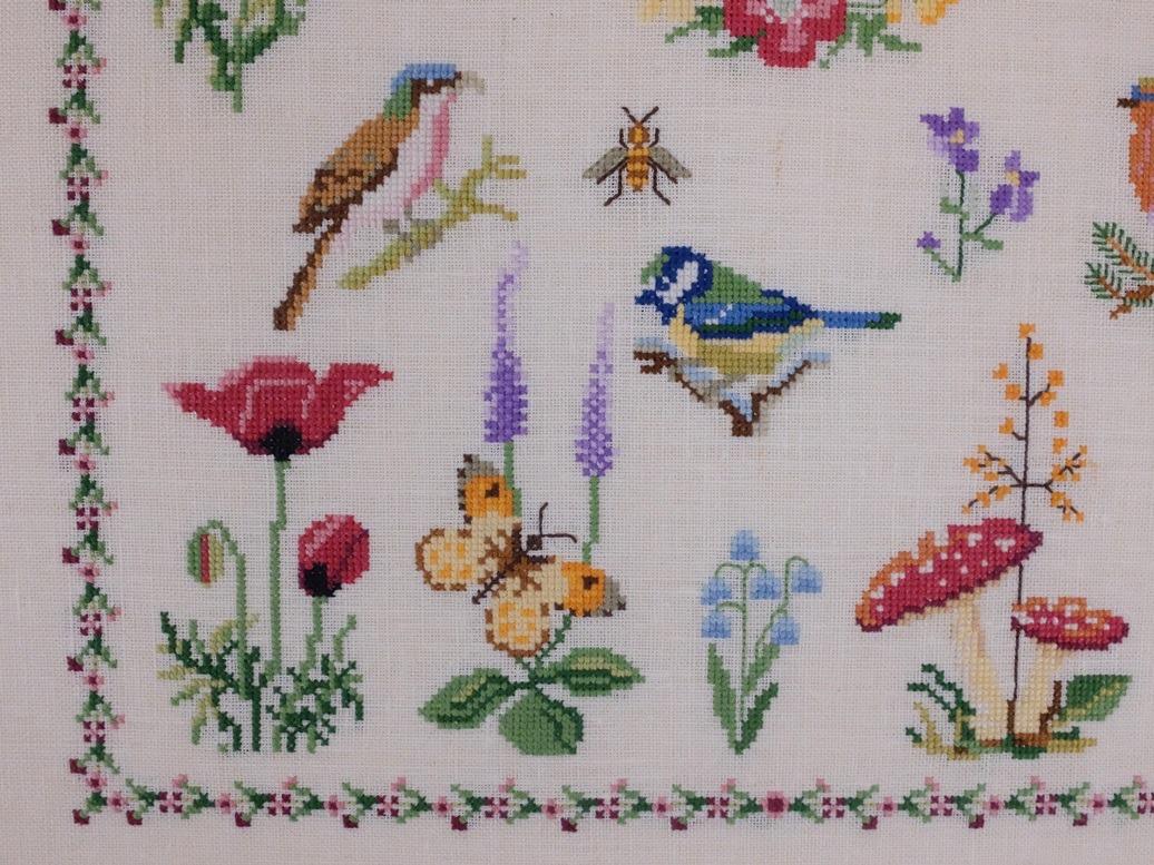 Detail borduurwerk vogeltjes vlinders bloemen