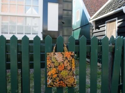Gebloemd tasje aan hek