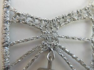 Detail zilverhaakwerk kerstklokjes