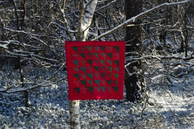 Rood quiltje in besneeuwd bos