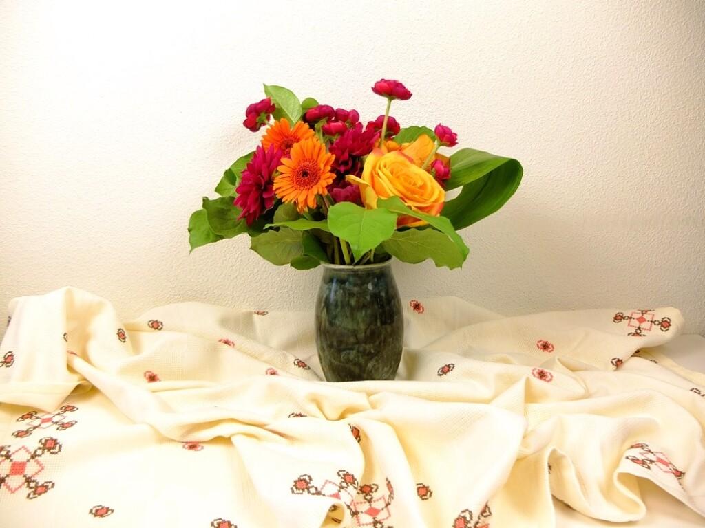 Vaas met bloemen op geborduurd tafelkleed