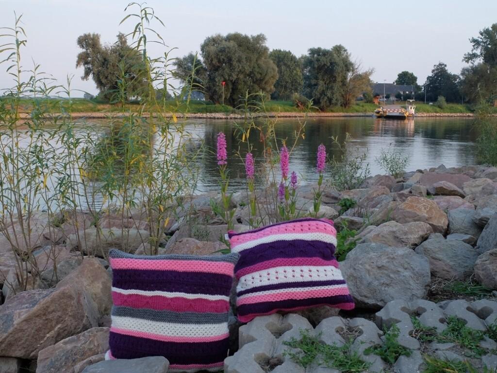 Twee gebreide kussens langs rivier